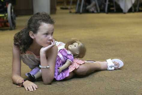Kathleen McDaniel, 9, of Overland Park and her American Girl doll watched the entertainment Sunday at the thrid annual American Girl Tea Party at the Regnier Center at Johnson County Community College.